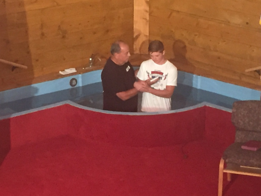 Young man getting baptized